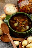 picture of chanterelle mushroom  - Delicious Vegetarian Soup with Chanterelle Mushrooms in Green Pot and Raw Ingredients with Wooden Spoons on closeup Rustic Wooden background - JPG