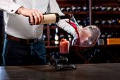 picture of wine cellar  - Sommelier pouring wine to the decanter in the wine cellar - JPG