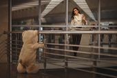 image of say goodbye  - Sad girl waving she says goodbye with a teddy bear and it - JPG