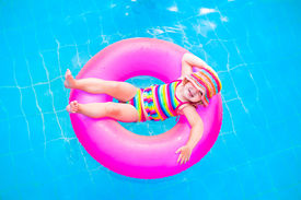 pic of floating  - Cute funny little toddler girl in a colorful swimming suit and hat relaxing on an inflatable toy ring floating in a pool having fun during summer vacation in a tropical resort - JPG