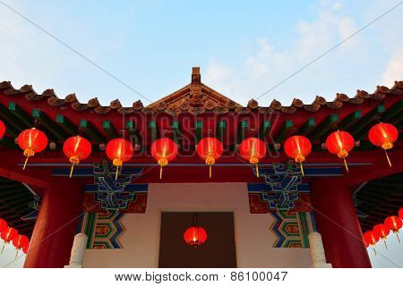 Red lanterns hanging on a Chinese Gazebo roof tile