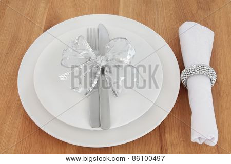 Place setting with  white plate, knife, fork and napkin with silver ring and bow over oak table background.