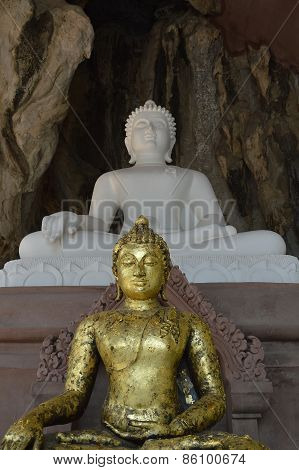 gold Buddha in front of white Buddha