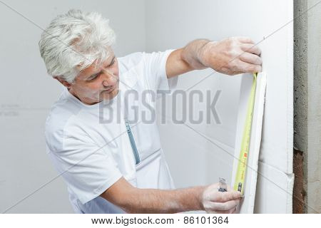 Mason measuring a wall