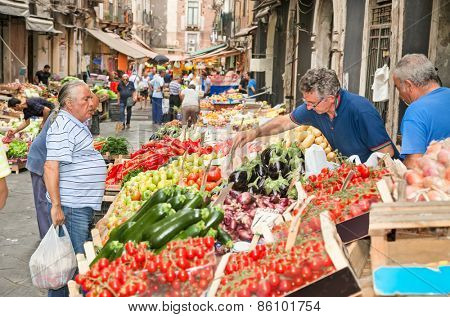 CATANIA, ITALY- SEP 17,2014: Unidentified costumers and sellers in the historical street market in Catania on Sep 17, 2014, Italy. This market has a history of several centuries.