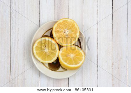 Overhead shot of three lemon halves in a bowl on a rustic whitewashed kitchen table. Horizontal format with copy space.