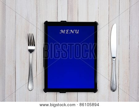 Tablet computer with menu on the screen on a rustic wood restaurant table. Electronic food service ordering concept.