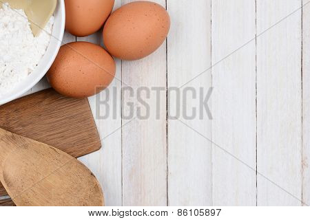 High angle shot of a baking still life, The objects, flour bowl, brown eggs and wood utensils are in the upper left corner and side, leaving plenty of copy space.