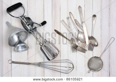 Overhead shot of a group of old kitchen utensils on a rustic wood kitchen table.