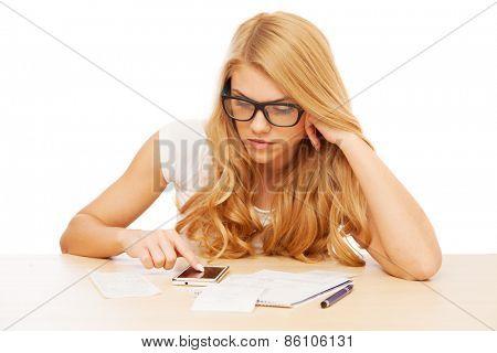 Young beautiful woman doing her accounts.