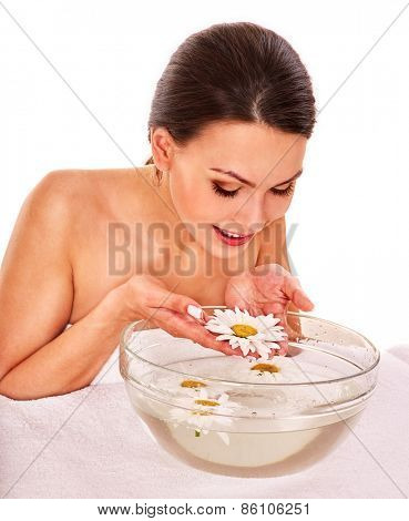 Facial massage with herbal facial treatment. Bowl with water and flowers of camomile. Isolated.
