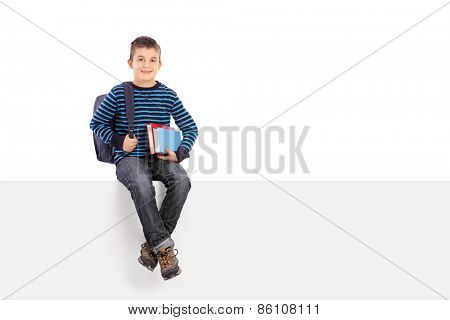 Studio shot of a schoolboy holding a couple of books and carrying a backpack seated on a blank signboard isolated on white background
