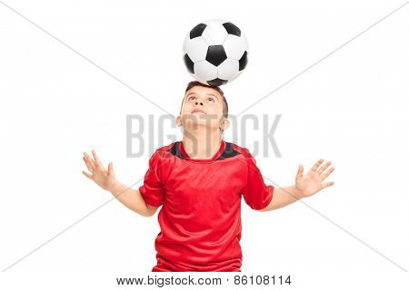 Junior soccer player wearing red shirt joggling with a soccerball isolated on white background