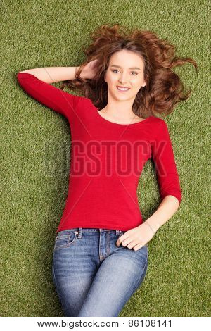 Vertical shot of a beautiful carefree woman lying in a field on the grass