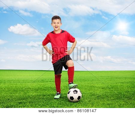 Full length portrait of a cheerful youngster standing over a football on a green field on a sunny summer day. Shot with tilt and shift lens