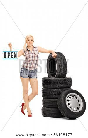Full length portrait of a blond woman standing next to a stack of tires and holding an open sign, isolated on white background, studio shot