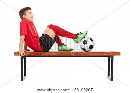 Relaxed young boy in football uniform sitting on a wooden bench and thinking isolated on white background