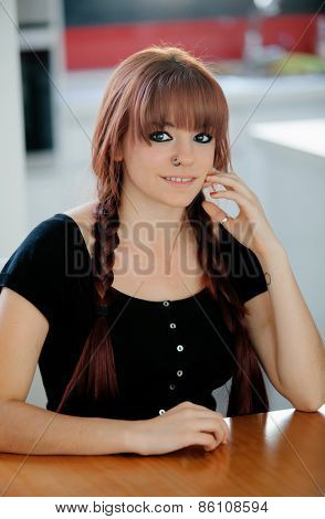 Rebellious teenager girl with red hair sit on the kitchen at home