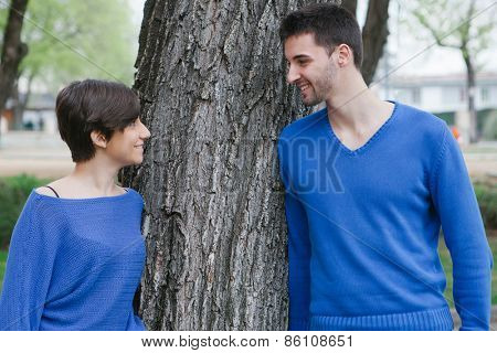 Young lovers dressed in blue supported on a  tree at the park