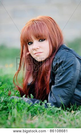 Rebellious teenager girl with red hair lying on the grass