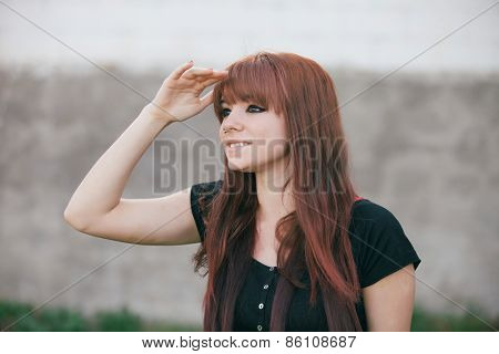 Rebellious teenager girl with red hair looking at side