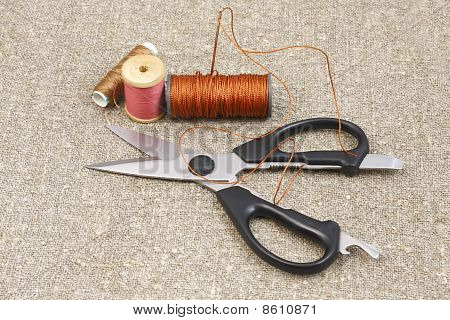 Scissors, Needle And Thread On Canvas Of Mats