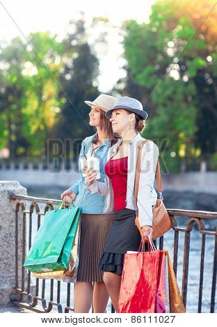 Two Beautiful Girls With Shopping Bags And Cup Of Coffee In The City