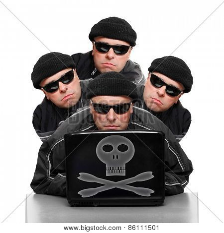 Group of anonymous hackers or terrorists with laptop.
