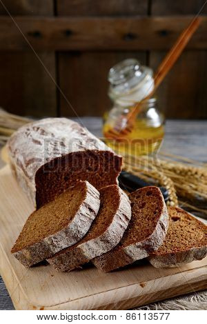 Bread Sliced Into Pieces And Honey On The Cutting Board