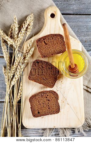 Slices Of Black Bread, Honey And Wheat Spikelets