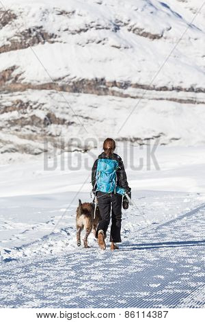 Woman With Dog Hiking In Winter
