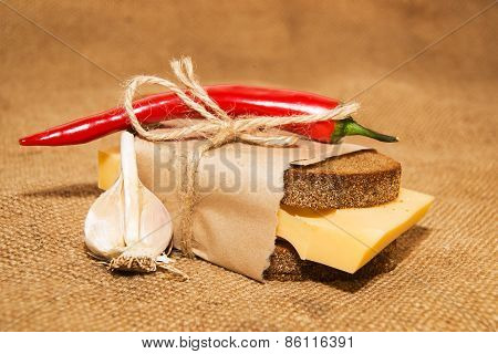 Sandwich With Cheese Wrapped In Paper, Chili Pepper And Garlic On Old Cloth