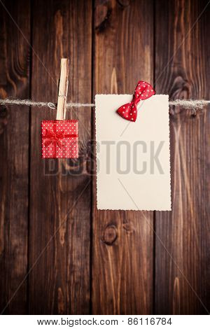 Old Paper Sheet With Bow And Small Gift Box Hanging On Clothesline Against Wooden Background