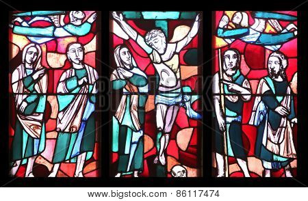 ELLWANGEN, GERMANY - MAY 07: Crucifixion, stained glass window in Basilica of St. Vitus in Ellwangen, Germany on May 07, 2014.