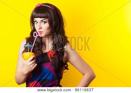 Beautiful Young Woman Wearing Earrings Made From Orange And Drinking Juice From An Orange Against Ye