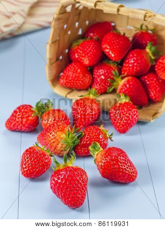 Basket With Strawberries Spilling On A Table