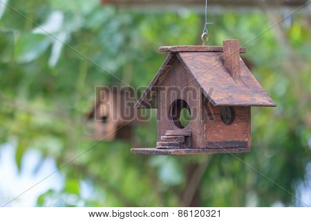 Two Wooden Bird Houses, One In Focus, One Out.