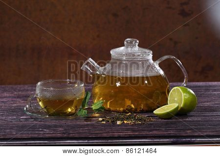 Tea In A Glass Teapot And A Transparent Cup With Lime And Mint On A Wooden Table