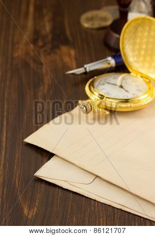 watch and old envelope on wooden background