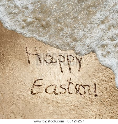 Concept or conceptual hand made or handwritten Happy Easter text in sand on a beach in an exotic island