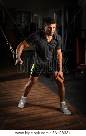 Young man doing one arm standing high cable fly