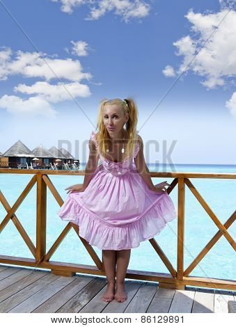 Young beautiful girl stands in pink sundress on sundeck of villa on water Maldives