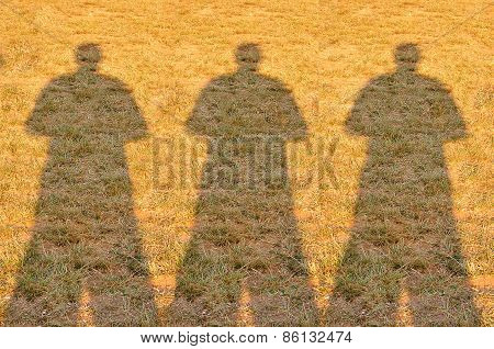Shadow Of Three Photographer Man On Field