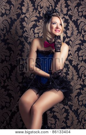 Beautiful Cabaret Woman Posing On A Chair Against Retro Wallpapers