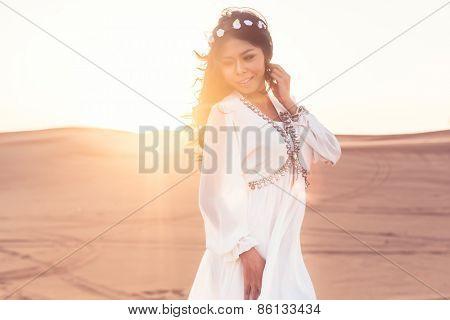 Beautiful girl standing in desert sunset