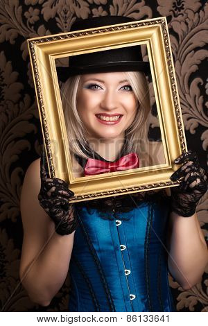 Beautiful Cabaret Woman Posing With Golden Frame Against Retro Wallpapers