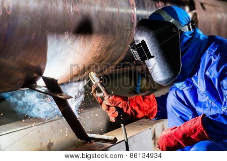 Welder in factory welding metal pipes