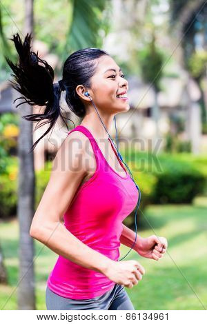 Asian woman running in park for fitness and sport, tropical setting
