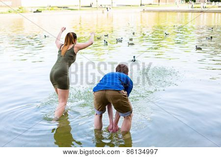 Couple romping cheerful in lake water