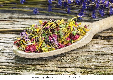 Natural dry herbal tea with meadow flowers on a wood